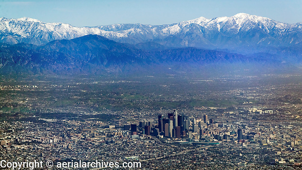 aerial photograph of the Los Angeles,  California skyline with snow covered mountains