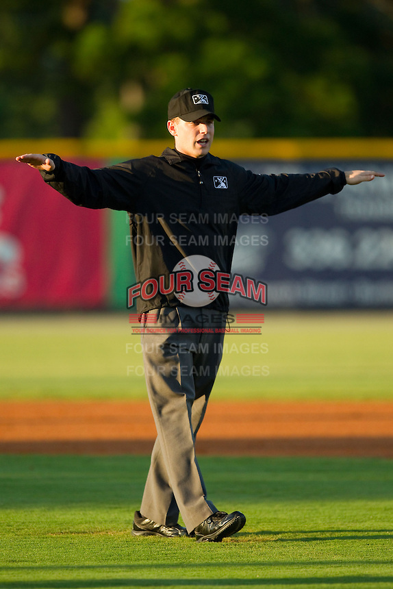 Umpire Skylar Shown makes a safe call on a play at first base during the Appalachian League game between the Danville Braves and the Burlington Royals at Burlington Athletic Park on August 16, 2013 in Burlington, North Carolina.  The Royals defeated the Braves 1-0.  (Brian Westerholt/Four Seam Images)