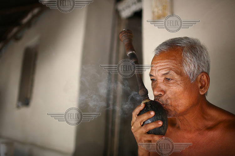 A Garo man smoking a traditional water pipe. The Garo (or Mandi, as they refer to themselves) are an ethnic minority thought to be of Tibeto-Burmese origin. Prior to British rule they were mostly anamists but missionary work led the majority to convert to Christianity. The Garo of the Madhupur forest have long been under the threat of eviction by the government and the forest that they gain much of their livelihood from is being rapidly destroyed by unregulated logging.