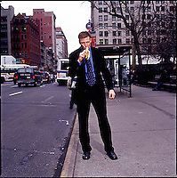 Man in suit standing on sidewalk eating a banana