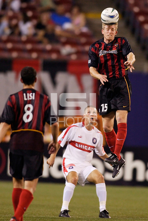 The  MetroStars' John Wolyniec goes up for a header as teammate  Mark Lisi the Chicago Fire's Logan Pause watch. The Chicago Fire played the NY/NJ MetroStars to a one all tie at Giant's Stadium, East Rutherford, NJ, on May 15, 2004.