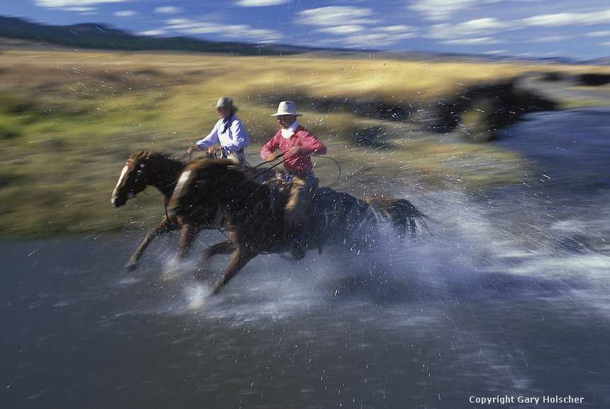 Cowboys on horses through stream. Ponderosa Ranch. Senaca OR. MR