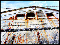 barbed wire/chain link fence around abandoned building