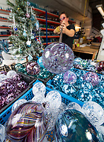 BNPS.co.uk (01202 558833)<br /> Pic:PhilYeomans/BNPS<br /> <br /> Each bauble is hand blown at the Bath factory.<br /> <br /> I'm forever blowing Baubles...!<br /> <br /> Britain's biggest hand blown Christmas bauble factory is working flat out at this time of year to keep up with demand for the festive favourite.<br /> <br /> 10,000 baubles are blown and individually signed every year at Bath Aqua Glass using raw silica for the blue tinged glass that is then coated with a mixture of copper, iron, manganese or even gold oxide to create colourful and unique designs.<br /> <br /> Evidence of glass making dating back to Roman times have been discovered in the historic Somerset town and boss Annette Dolan keeps the tradition alive with the delicate creations being sent all over the world.