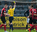 Dundee's James McPake is booked by Referee Bobby Madden after a penalty was awarded to St Johnstone.