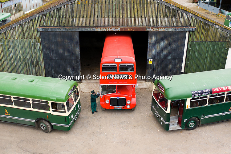 Pictured: James Freeman, Chairman of The Friends of King Alfred Buses polishes the wing mirror of a red 1964 AEC Renown vintage bus no. 596, sandwiched between a green 1950 Leyland Olympic no. 708 and a 1959 Leyland Tiger no. 104 at the bus depot near Romsey, Hants during what would typically be a busy period leading up to the King Alfred Buses Running Day event, which has been cancelled this year due to the coronavirus pandemic. <br /> 