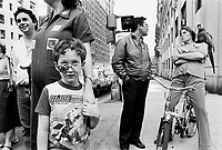 """USA. New York City. Life on the street. A boy with funky glasses wears a GI Joe T-shirt. Her mother wears work clothes with the logo of Esso ( petrol gas station) and a tiger. Put a tiger in your tank was a popular Esso advertising slogan. A woman seated on a bicycle has a parrot standing on her shoulder and talks to a man. Roas sign """" Don't walk"""". G.I. Joe is a line of action figures produced by the toy company Hasbro. Although the members of the G.I. Joe team are not superheroes, they all had expertise in areas such as martial arts, weapons and explosives. Esso is an international trade name for ExxonMobil and its related companies. © 1986 Didier Ruef"""