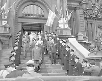 Le general  Charles de Gaulle descendant les marches extérieures de l'hotel de ville suivi du maire Sarto Fournier et de leurs epouses. On y voit une haie d'honneur de policiers de la Ville de Montréal de même que les drapeaux ornant l'entrée principale de l'hôtel de ville.