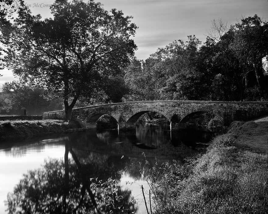 """""""Morning at Burnside Bridge""""<br /> Antietam National Battlefield<br /> Sharpsburg, Maryland<br />  2014<br /> Peaceful waters reflect the sturdy limestone arches of Burnside Bridge, located southeast of Sharpsburg, Maryland.   Built in 1836 as a crossing of Antietam Creek, the bridge witnessed the daunting task of a Union attack on the Confederate infantry and artillery in 1862.  A sycamore tree provides a respite just as it did for battle-weary soldiers over 150 years ago."""