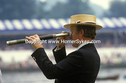 Straw boaters 1980s. Henley Royal Rowing, Regatta Henley on Thames Berkshire. Man using a telescope to watch the rowing  UK 1985.