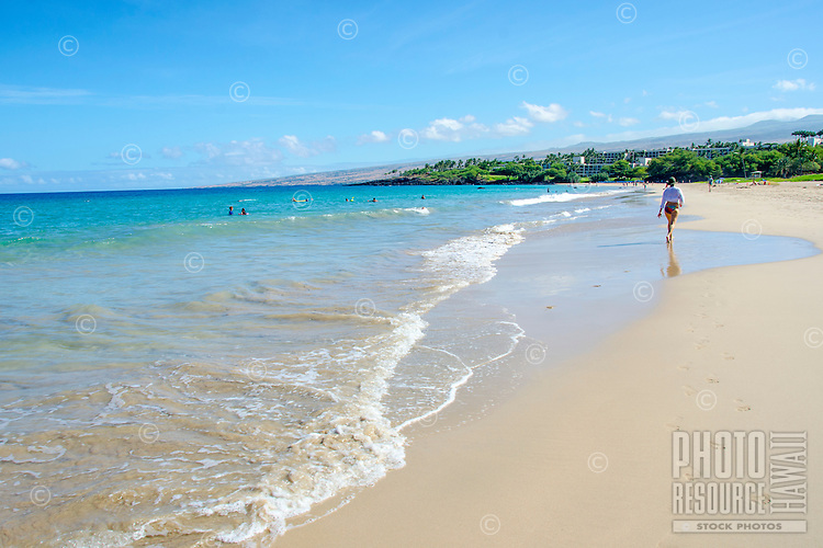 Woman walking along Hapuna Beach, along the Big Island's Kohala Coast. This white sand beach has been rated one of the best beaches in the world time and time again.