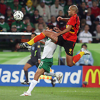 Angola's Kali (right) goes over Mexico's Jesus Arellano (21) for the ball. Mexico and Angola played to a 0-0 tie in their FIFA World Cup Group D match at FIFA World Cup Stadium, Hanover, Germany, June 16, 2006.