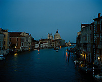 Dusk on the Grand Canal in Venice. The domes of the Baroque church Santa Maria della Salute stand tall in the centre of the frame