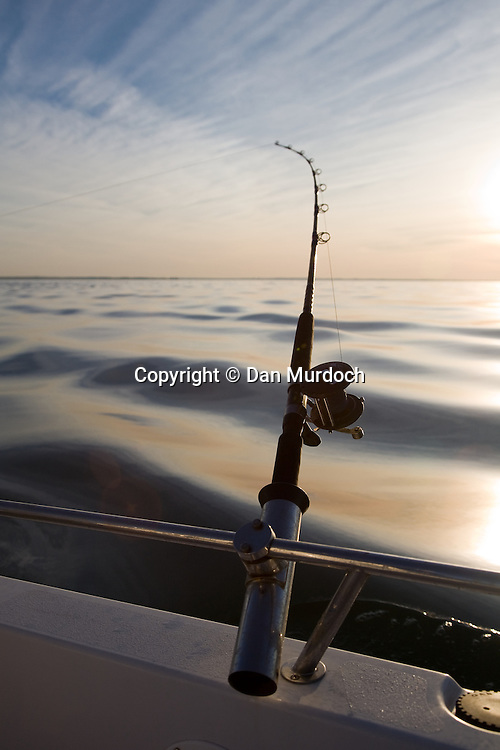 Beautiful sunset and flat water behind bent fishing rod. Set of 2