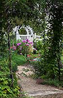 Gravel path through arbor leading to secret garden and entry gate of Minnesota garden
