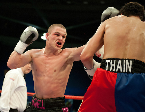 GLASGOW, SCOTLAND - MARCH 10: John Thain (red, white and blue shorts) punched by Joe Lovell (black and pink shorts) in a light-middleweight contest on the Ricky Burns undercard at the Braehead Arena on March 10, 2012 in Glasgow, Scotland. (Photo by Rob Casey/Getty Images)