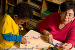 Preschool Headstart 3-5 year olds female teacher working with 3 year old boy on cutting and pasting activity horizontal art activity