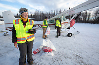 Volunteers, Leslie Washburn and John Hooley help Volunteer Iditarod Air Force pilot, Monte Mabry load his plane with musher drop bags at the Willow, Alaska airport during the Food Flyout on Saturday, February 20, 2016.  Iditarod 2016