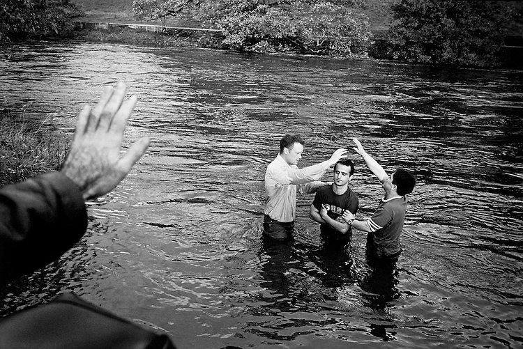 © John Angerson.A Jesus Army elder facilitates the Baptism of Iranian asylum seeker in the River Wharf, North Yorkshire. Many persecuted Christians from across the globe have found refuge in the Jesus Army..