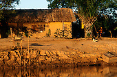 Pantanal, Brazil. Wattle and daub adobe palm thatched house beside a river in golden evening light.