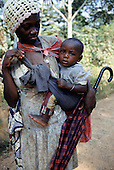 La Gongue, Gabon. Young Gabonese women with her baby son in a sling holding an umberella.