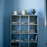 Piles of papers are arranged on the shelves of a freestanding grey painted cubed display unit.