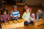 Education elementary school grade 1 group of children playing music, making rhythm piece together