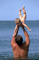A father tosses his smiling infant son into the air as they enjoy a swim at the beach.
