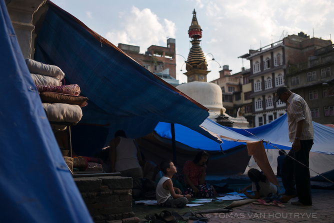A boy pauses while doing his homework under a shelter made of tarps at Yetkha Bahal, an area of Kathmandu where homes were made unsafe by the earthquake in Kathmandu, Nepal in June 2015.