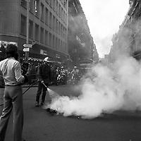 Carrefour de l'avenue d'Alsace-Lorraine et de la rue Lafayette. 5 septembre 1975. Au 1er plan photographe de dos, pompier éteignant un feu (pneus) au milieu de la route, fumée ; au 2nd plan deux policiers à moto bloquent la circulation, foule sur le trottoir à l'angle de la rue regarde la scène ; en arrière-plan vue perspective de l'avenue d'Alsace-Lorraine en direction des boulevards, plan d'ensemble des façades, bus. Cliché pris lors d'une manifestation contre le Général Franco.
