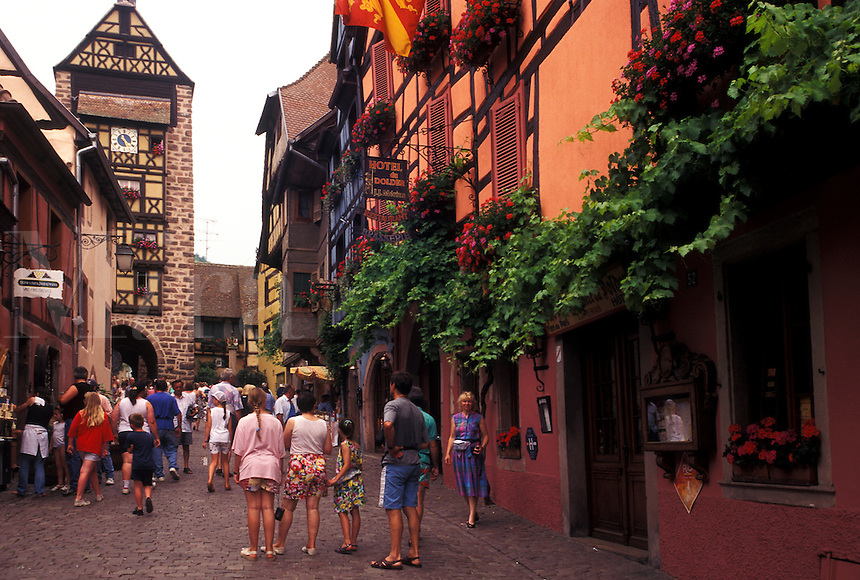 France, Alsace, Riquerwihr, Haut-Rhin, Europe, wine region, People walking on the cobbled streets surrounded by half-timbered buildings in the picturesque village of Riquerwihr in the wine region of Alsace.