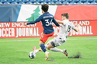 FOXBOROUGH, MA - APRIL 17: Jalen Crisler #15 of Richmond Kickers slides to tackle Ryan Spaulding #34 of New England Revolution II during a game between Richmond Kickers and Revolution II at Gillette Stadium on April 17, 2021 in Foxborough, Massachusetts.