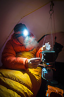 Climber melts pure glacier ice for drinking water inside a tent, Iceland