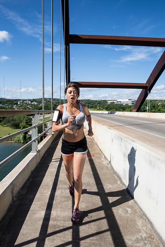 Sporty African-American female running on the 360 Bridge on Lake Austin, Texas.