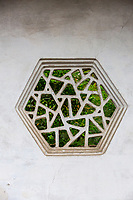 Suzhou, Jiangsu, China.  Hexagonal Window in Garden Wall, House of the Master of the Nets.