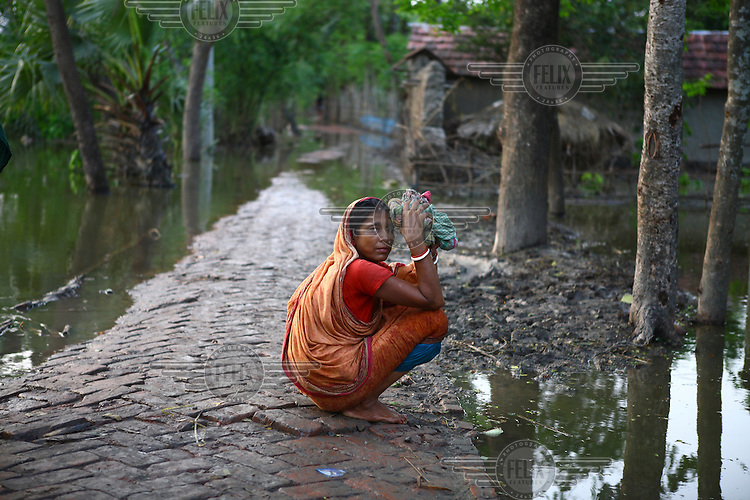 A woman squats beside the floodwaters. Thousands of people were displaced in Shyamnagar Upazila, Satkhira district after Cyclone Aila struck Bangladesh on 25/05/2009, triggering tidal surges and floods..