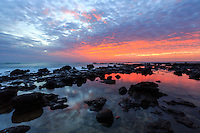A majestic sunrise lights up tide pools caught in the rocky coastline around Anahola Bay, Kaua'i.