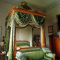 An imposing Regency domed bed, measuring 7 foot by 7 foot and draped in green silk, dominates the Chintz Bedroom