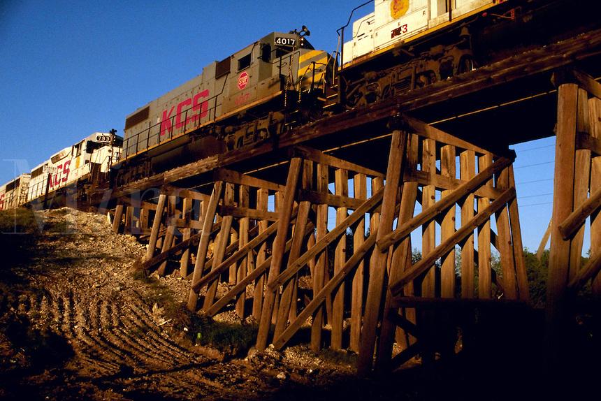 Railroad locomotives pull a train across a bridge, or trestle.