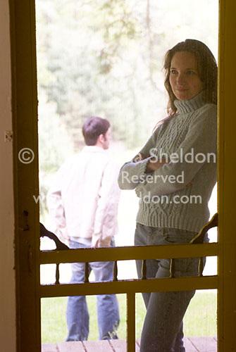 Woman leaning screen door, man in background<br />