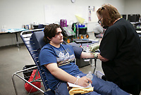 Donor specialist Donna Perkins (right) draws blood from Ean Robertson (center), Monday, April 26, 2021 at Rogers New Tech High School in Rogers. The Community Blood Center of the Ozarks held a student organized blood drive with the goal of collecting 49 units at the school. The school's student leadership promoted the event through videos and social media and helped check-in donors. They will have another drive on Wednesday at the Siloam Springs Regional Hospital and two others in Rogers at the Water Utilities on Friday and the First United Methodist Church on Saturday. Check out nwaonline.com/210427Daily/ for today's photo gallery. <br /> (NWA Democrat-Gazette/Charlie Kaijo)