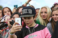 London, UK on Sunday 31st August, 2014. Leondre from Bars & Melody takes a selfie on a fan's phone during the Soccer Six charity celebrity football tournament at Mile End Stadium, London.
