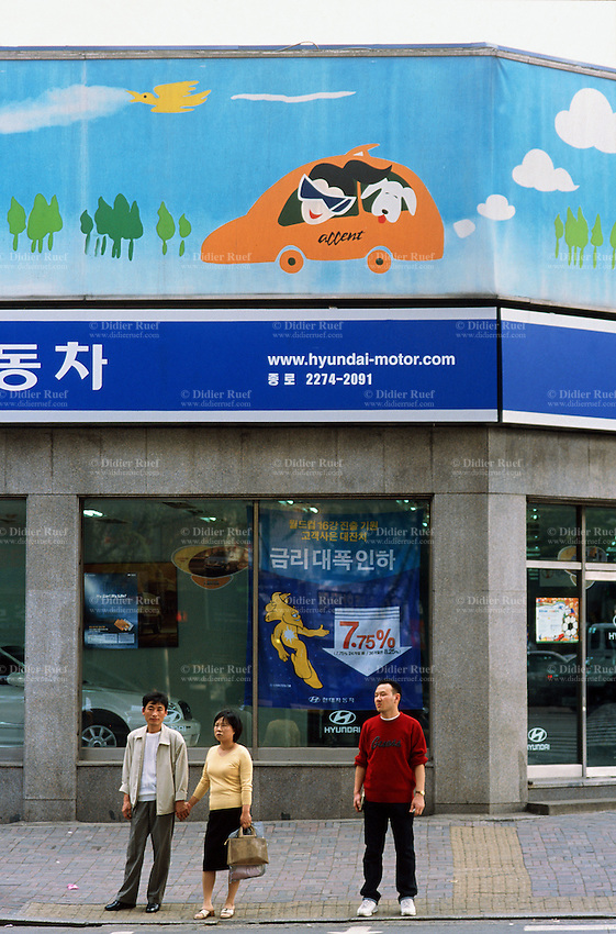 Korea. South Korea.  Seoul. Advertisement fixed on the walls in the street for the korean Hyunday car manufacturer.  Shop selling automobiles. A family and its pet uses the last new model. © 2002 Didier Ruef