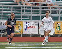 Boston Aztec forward Lucy Gildein (27) brings the ball forward.  In a Women's Premier Soccer League (WPSL) match, Boston Aztec (white) defeated Seacoast United Phantoms (blue), 3-0, at North Reading High School Stadium on Arthur J. Kenney Athletic Field on on June 25, 2013.
