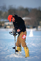 A fisherman drills a hole for ice fishing.