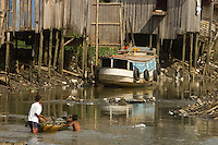 Ronaldo Vilhena 34  anos, morando a 20  no Tucunduba, a falta de água encanada lhe faz usar uma bica a 10 mts do igarapé, pequeno rio, cuja a ocupação desordenada ha várias decadas levaram a degradação do meio ambiente e baixa qualidade de vida.<br /> As famílias moradoras da área não tem acesso a água encanada. <br /> O igarapé que fica a cerca de 150 km do litoral paraense no atlântico sofre influência da maré , servindo para transporte para alguns bairros da cidade só pode ser usado durante a alta maré.<br /> Belém Pará Brasil<br /> 05/06/2004<br /> Foto Paulo Santos/Interfoto