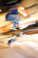 A skateboarder does a kick flip on a ramp.