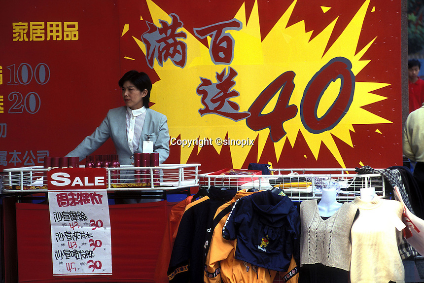 A saleswoman stands behind a counter at a sale in a downtown store in Shanghai, China.