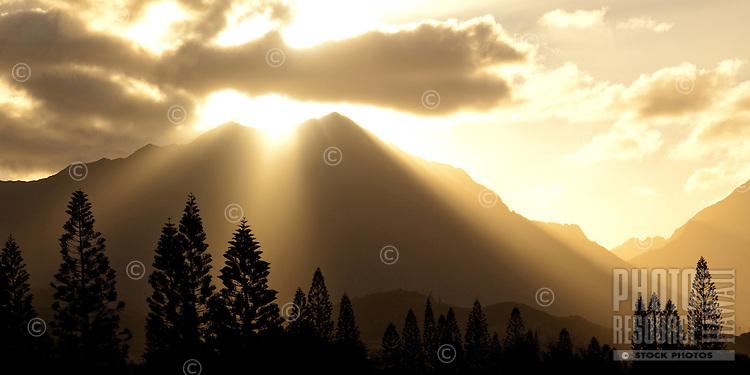 Rays of light shine through the clouds as the sun sets behind the Ko'olau Mountain Range in Kailua, O'ahu.