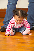 MR / Schenectady, NY. Infant (girl, 12 months, African American & Caucasian) having temper tantrum while sitting on the floor at her mother's feet. MR: Dal4. ID: AL-HD. © Ellen B. Senisi